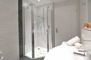 Blick ins Bad, mit Dusche, Waschtisch und WC